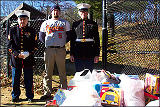Toys for Tots representatives from the U.S. Marines, Jack McDonald and Paul Nolan, pose with Tim Fish of the MABL Orioles, who is also a 6-year veteran of the U.S. Marines